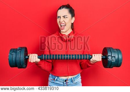 Beautiful woman with blue eyes wearing sportswear using dumbbells angry and mad screaming frustrated and furious, shouting with anger. rage and aggressive concept.