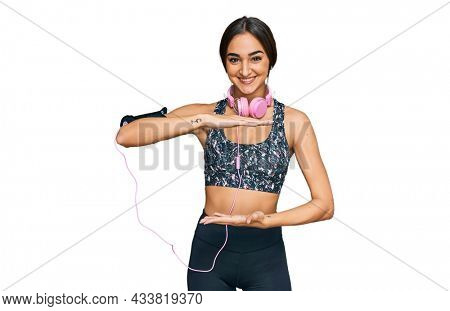 Beautiful brunette woman wearing gym clothes and using headphones gesturing with hands showing big and large size sign, measure symbol. smiling looking at the camera. measuring concept.