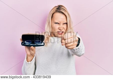 Beautiful caucasian blonde woman holding glasses in eyewear case annoyed and frustrated shouting with anger, yelling crazy with anger and hand raised