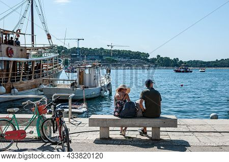 Couple Of Tourists Sit By The Sea On The Central Square Of Rovinj, Croatia, August 30, 2018, In The