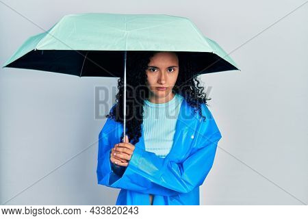 Young hispanic woman with curly hair wearing a raincoat and umbrella skeptic and nervous, frowning upset because of problem. negative person.