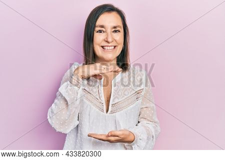 Middle age hispanic woman wearing casual clothes gesturing with hands showing big and large size sign, measure symbol. smiling looking at the camera. measuring concept.