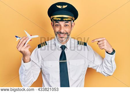 Handsome middle age man with grey hair wearing airplane pilot uniform holding toy plane pointing finger to one self smiling happy and proud