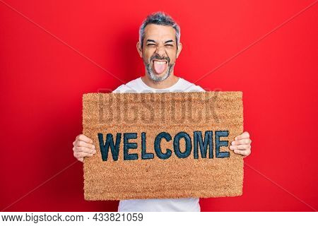 Handsome middle age man with grey hair holding welcome doormat sticking tongue out happy with funny expression.