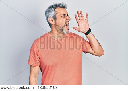Handsome middle age man with grey hair wearing casual t shirt shouting and screaming loud to side with hand on mouth. communication concept.