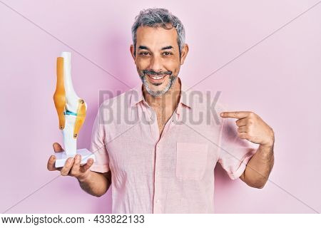 Handsome middle age man with grey hair holding anatomical model of knee joint pointing finger to one self smiling happy and proud
