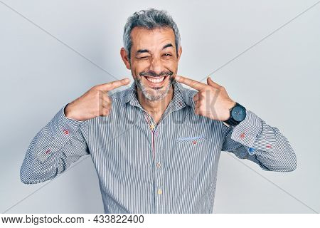 Handsome middle age man with grey hair pointing mouth with fingers winking looking at the camera with sexy expression, cheerful and happy face.