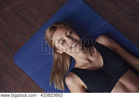 Young smiling european sportswoman laying and resting with closed eyes on fitness mat. Concept of healthy lifestyle. Beautiful blonde girl wearing sportswear. Dark room with wooden floor. Top view