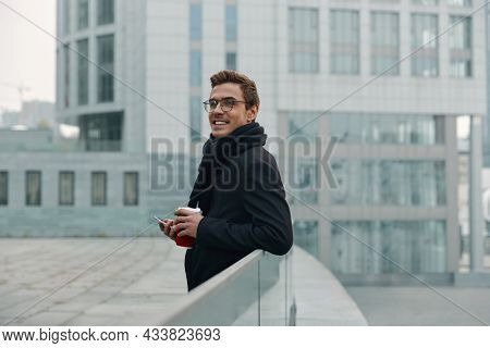 Young smiling european businessman with coffee cup and mobile phone on balcony of modern building. Concept of modern successful man. Handsome stylish guy wearing scarf, coat and glasses. City daytime