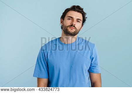 Young brunette man with bristle posing and looking at camera isolated over blue background