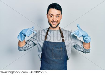 Young hispanic man wearing apron and gloves looking confident with smile on face, pointing oneself with fingers proud and happy.