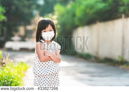 Adorable Female Child Wearing White Face Mask Looking At Camera. Girl Keeping Arms Folded, Feeling H