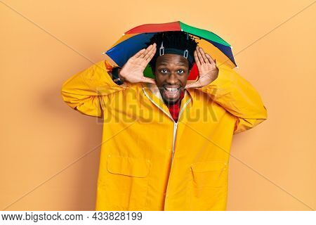 Young african american man wearing yellow raincoat smiling cheerful playing peek a boo with hands showing face. surprised and exited