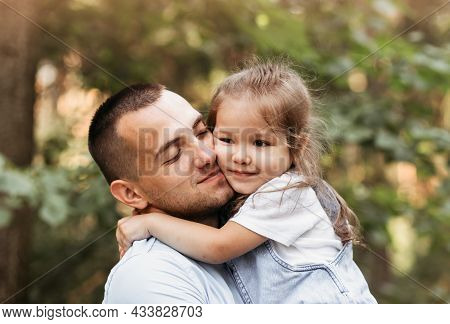 A Young Father Hugs His Young Daughter In Nature. Hugs And Kisses