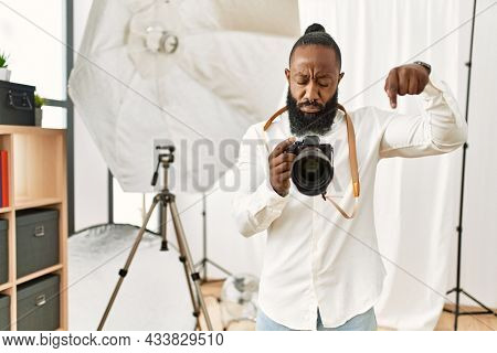 African american photographer man working at photography studio pointing down looking sad and upset, indicating direction with fingers, unhappy and depressed.