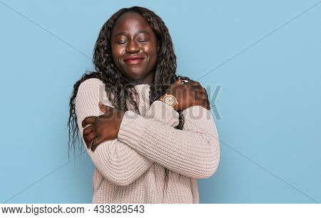 Young african woman wearing wool winter sweater hugging oneself happy and positive, smiling confident. self love and self care