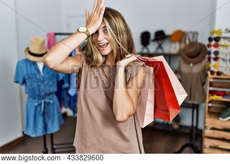 Young blonde woman holding shopping bags at retail shop surprised with hand on head for mistake, remember error. forgot, bad memory concept.