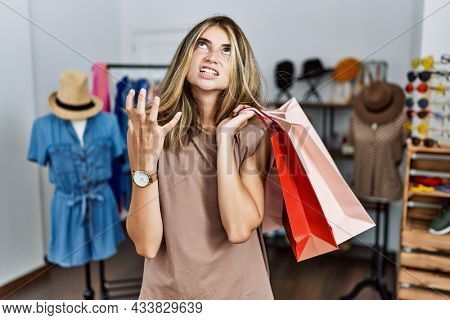 Young blonde woman holding shopping bags at retail shop crazy and mad shouting and yelling with aggressive expression and arms raised. frustration concept.