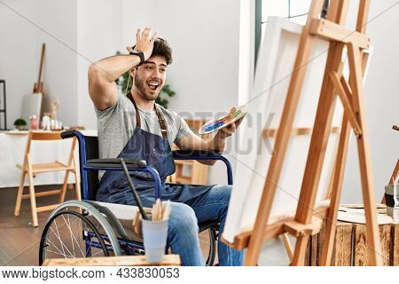 Young hispanic man sitting on wheelchair painting at art studio surprised with hand on head for mistake, remember error. forgot, bad memory concept.