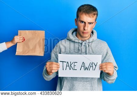Young caucasian man holding take away banner reciving delivery paper bag skeptic and nervous, frowning upset because of problem. negative person.