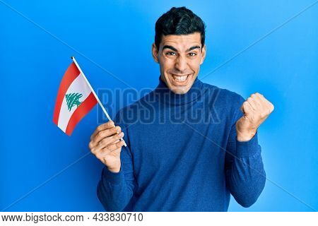 Handsome hispanic man holding lebanon flag screaming proud, celebrating victory and success very excited with raised arm