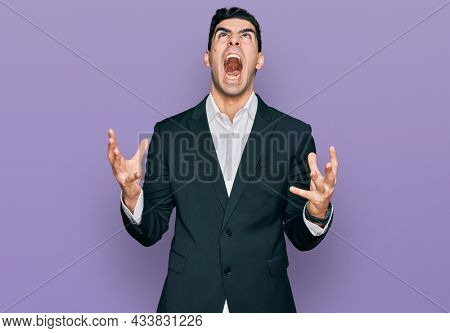Handsome hispanic man wearing business clothes crazy and mad shouting and yelling with aggressive expression and arms raised. frustration concept.