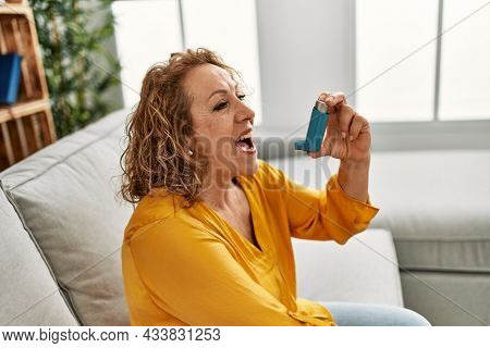 Middle age caucasian asthmatic woman using inhaler sitting on the sofa at home.