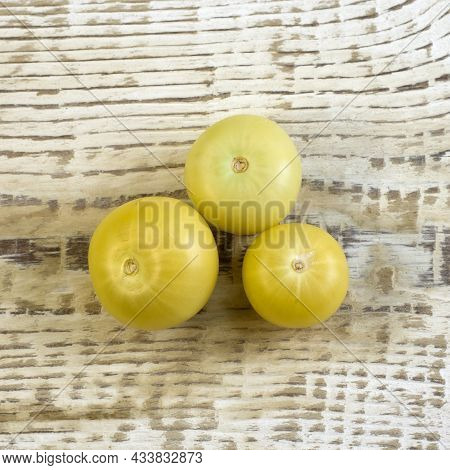 Bright Unripe Yellow Tonatoes Close Up Flat Lay Photo On White Textured Wooden Background Top View