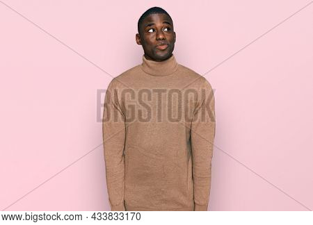 Young african american man wearing casual winter sweater smiling looking to the side and staring away thinking.
