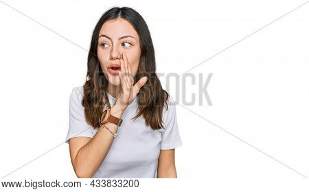 Young beautiful woman wearing casual white t shirt hand on mouth telling secret rumor, whispering malicious talk conversation