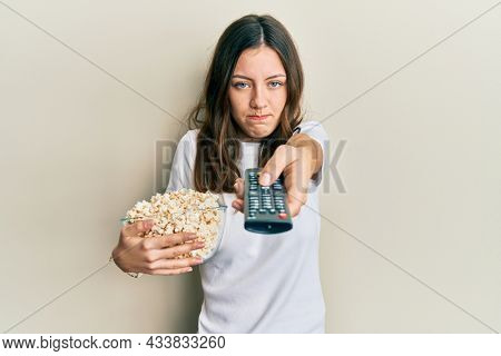 Young brunette woman eating popcorn using tv control skeptic and nervous, frowning upset because of problem. negative person.