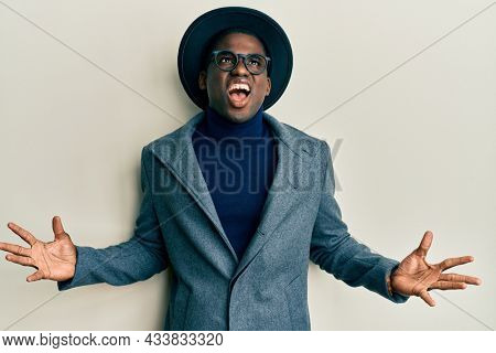 Young african american man wearing elegant style crazy and mad shouting and yelling with aggressive expression and arms raised. frustration concept.