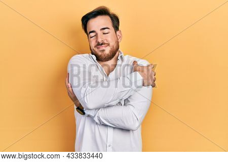 Handsome caucasian man with beard wearing business white shirt hugging oneself happy and positive, smiling confident. self love and self care