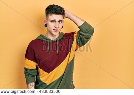 Young caucasian boy with ears dilation wearing casual sweatshirt confuse and wonder about question. uncertain with doubt, thinking with hand on head. pensive concept.