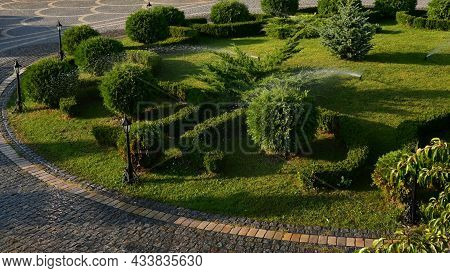 Garden Sprinklers Rotate And Watering Plants And Grass Of Round Landscaped Lawn With Retro Lantern S