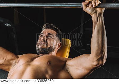 Man With An Expression Of Strength Doing Bench Presses Indoors