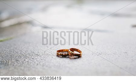 Two Gold Wedding Rings On A Stone Surface, Frontal View. Wedding, Marriage, Love Concept. Selective