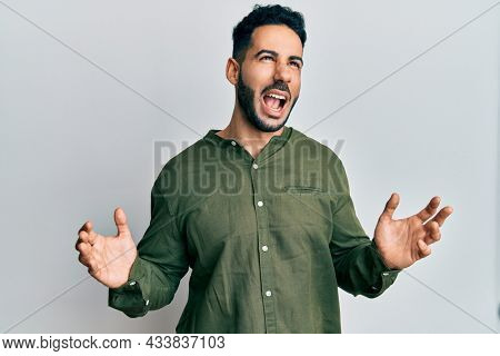 Young hispanic man wearing casual clothes crazy and mad shouting and yelling with aggressive expression and arms raised. frustration concept.