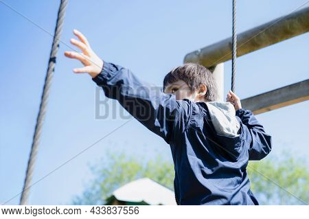 Active Kid Holding Rope Chains In Playground, Child Enjoying Outdoors Activity In A Climbing Chains