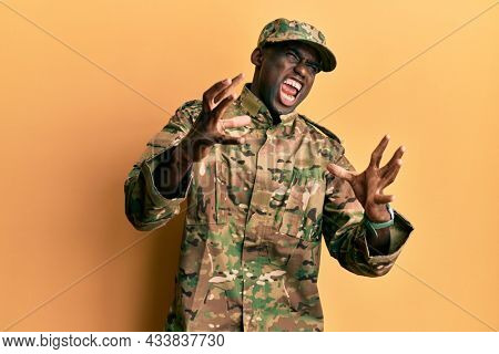 Young african american man wearing army uniform shouting frustrated with rage, hands trying to strangle, yelling mad