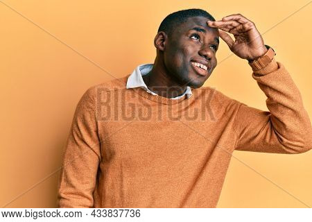 Young african american man wearing casual clothes very happy and smiling looking far away with hand over head. searching concept.