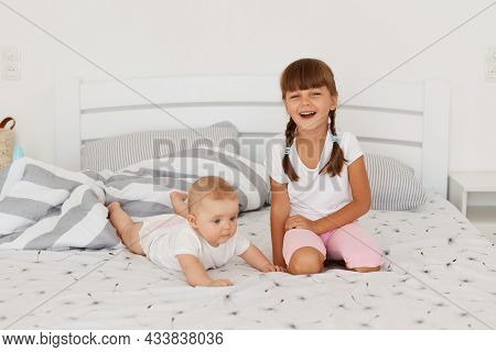 Two Sibling Playing At Home, Posing On Bed, Elder Child Looking Smiling Directly At Camera, Dark Hai