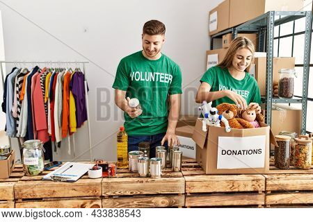 Young hispanic volunteer couple smiling happy working at charity center.
