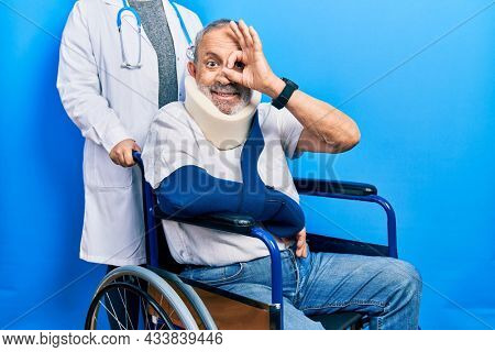 Handsome senior man with beard sitting on wheelchair with neck collar doing ok gesture with hand smiling, eye looking through fingers with happy face.
