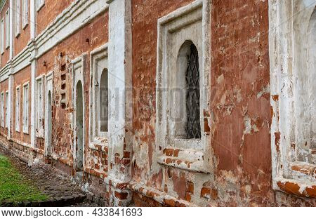 Old Shabby Facade Of The Building. Weathered And Red Painted Cement And Brick Wall. Painted Distress
