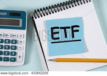 Etf ( Exchance Traded Fund) - Acronym In A White Notebook On A Blue Piece Of Paper On The Background