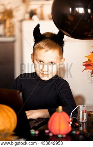 Funny Kid Boy In Evil Costume For Halloween Using A Digital Tablet Laptop Notebook. Online Call Frie
