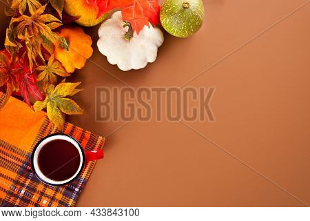 Composition With Red Mug With Tea, Autumn Leaves And Small Pumpkins On The Brawn Background. Autumn