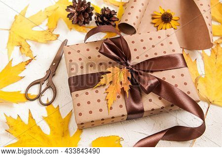 Gift Wrapping. Brown Paper Gift Box With Yellow Dried Leaves On White. Autumn Creative Holiday Prese