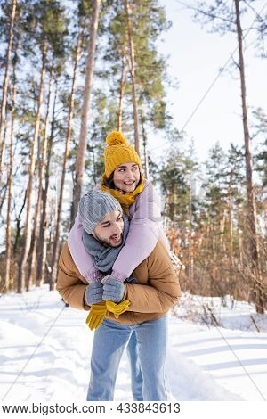 Cheerful Woman Embracing Boyfriend And Looking Away In Winter Park